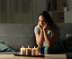 brownout vs blackout: woman sitting with candles during a power outage