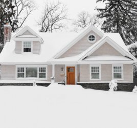 house covered in snow to depict the importance of how to winterize a vacant house
